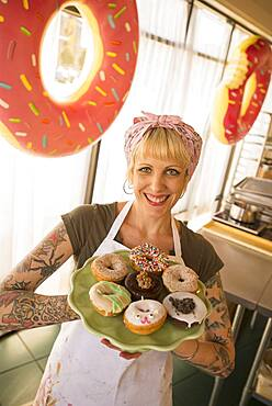 Asian baker holding plate of donuts in bakery