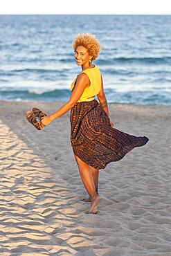 Black woman carrying sandals on beach
