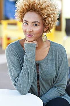 Black woman resting chin in hand outdoors