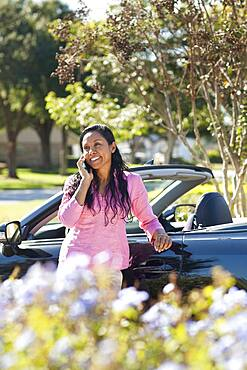 Indian woman talking on cell phone near car