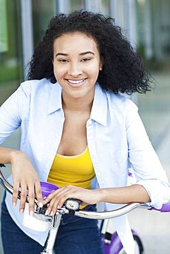 Smiling Black woman riding bicycle outdoors