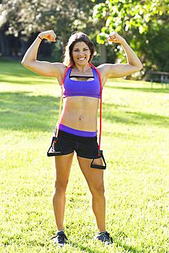 Caucasian athlete flexing muscles in park