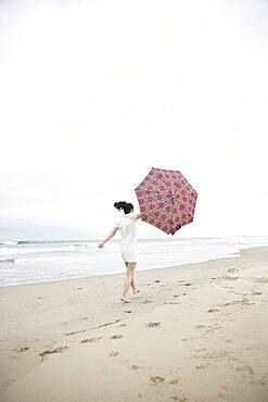 Woman walking in wind with umbrella on beach