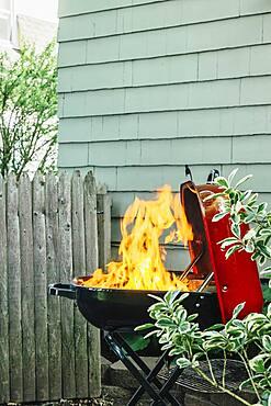 Fire burning on grill in backyard