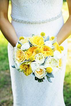 Caucasian bride holding bouquet outdoors