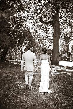Caucasian bride and groom walking on dirt path
