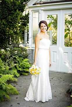 Caucasian bride holding bouquet in garden