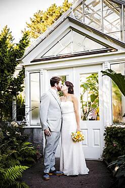 Caucasian bride and groom kissing in garden