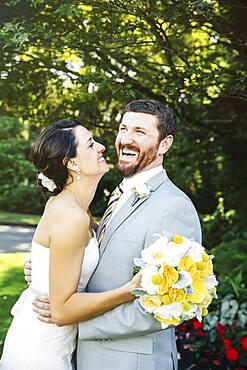 Caucasian bride and groom hugging in garden