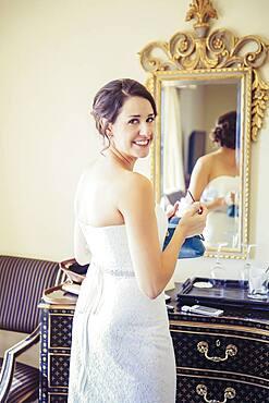 Caucasian bride applying makeup in mirror