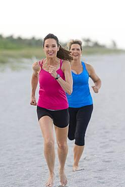 Caucasian women running on beach