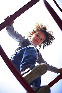 Low angle view of mixed race boy climbing on play structure