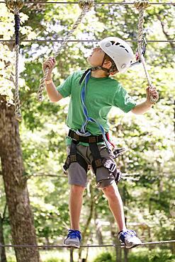 Caucasian boy balancing on slackline in forest