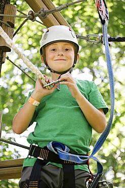 Caucasian boy hooking harness to line