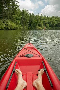 Caucasian teenage boy sitting in canoe on lake