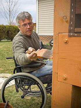 Caucasian paraplegic man painting deck in backyard