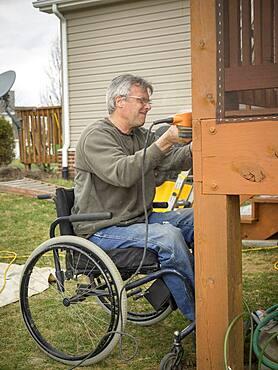 Caucasian paraplegic man wood working in backyard