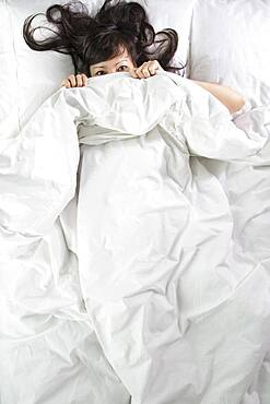Mixed race woman peeking out from bed blankets