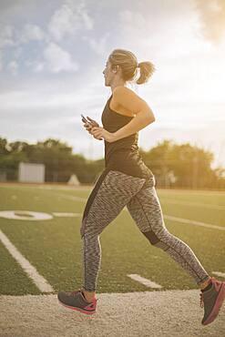 Caucasian athlete jogging on sports field