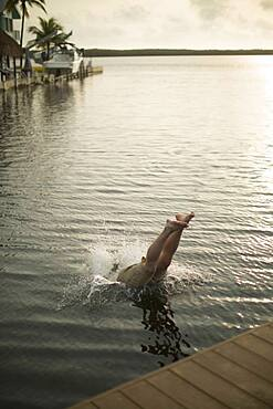 Mixed race woman diving into lake