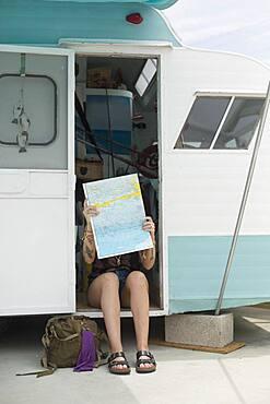 Caucasian woman reading map in trailer
