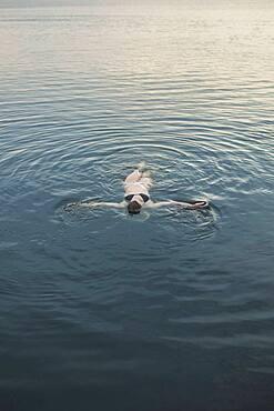 Caucasian woman floating in still lake