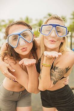 Caucasian women blowing kisses in snorkel masks