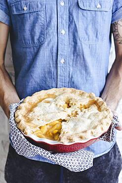Caucasian man holding peach pie