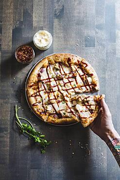 Hand choosing slice of pizza