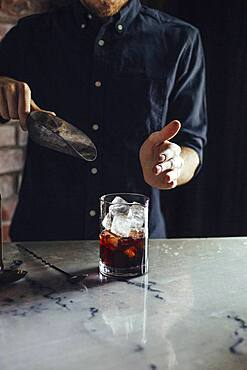 Caucasian bartender pouring ice in cocktail