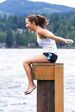 Mixed race girl sitting on wooden pedestal at lake