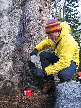 Caucasian hiker pouring coffee outdoors