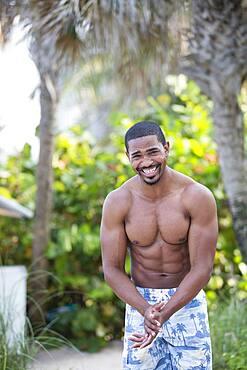 African American man wearing swim trunks on beach