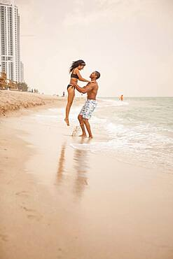 Man lifting girlfriend in ocean waves on beach