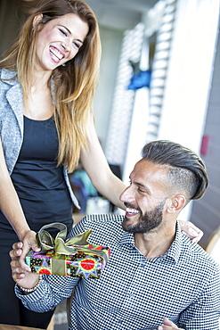 Hispanic woman giving boyfriend gift