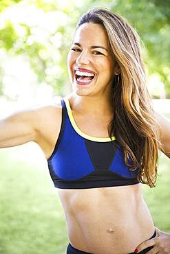 Mixed race woman flexing muscle