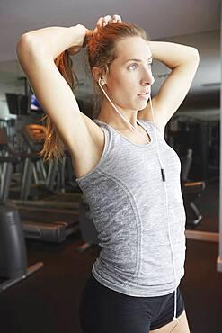 Woman tying hair in ponytail at gym