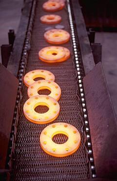 Glowing metal manufactured pieces on conveyor belt