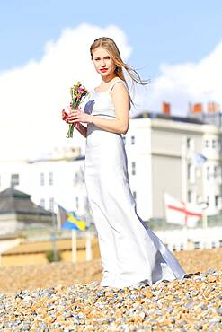 Woman holding bouquet on beach