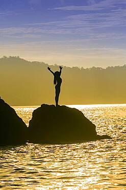 Mixed race woman standing on rock over ocean