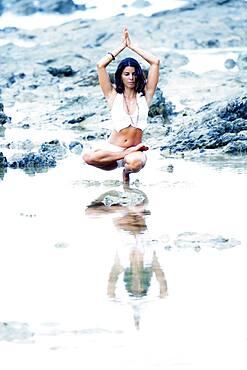 Woman practicing yoga in creek