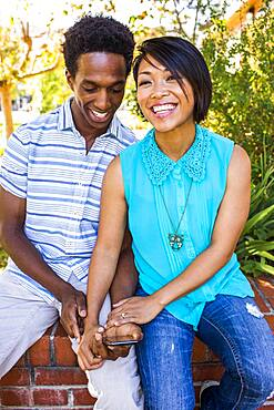 Smiling couple using cell phone outdoors