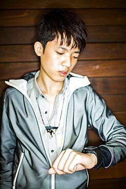 Asian man checking wristwatch