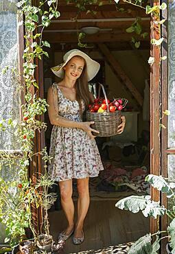Caucasian woman holding vegetable basket in doorway
