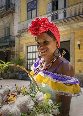 Hispanic woman carrying basket of flowers