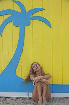Caucasian woman sitting near wall