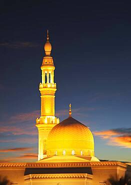 Illuminated pillar and dome under sunset sky