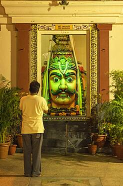 Man admiring statue in ornate temple