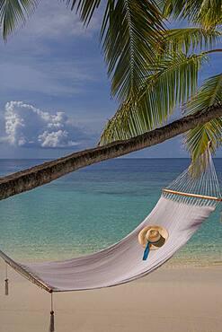 Sun hat in empty hammock on beach