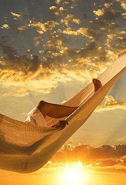 Caucasian woman laying in hammock at sunset